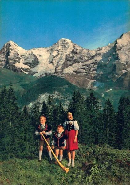 Berner Oberland. Trachtengruppe mit Blick auf Eiger, Mönsch und Jungfrau Vorderseite